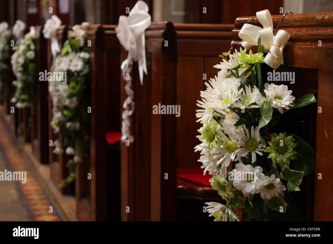 Church pews with wedding floral arrangements of flowers in green and Stock Photo Royalty Free