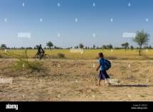 Girl Walking Barefoot to School Stock Photo