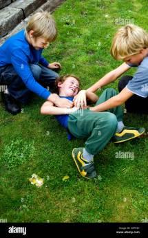 Two Male Children Tickling Child Stock