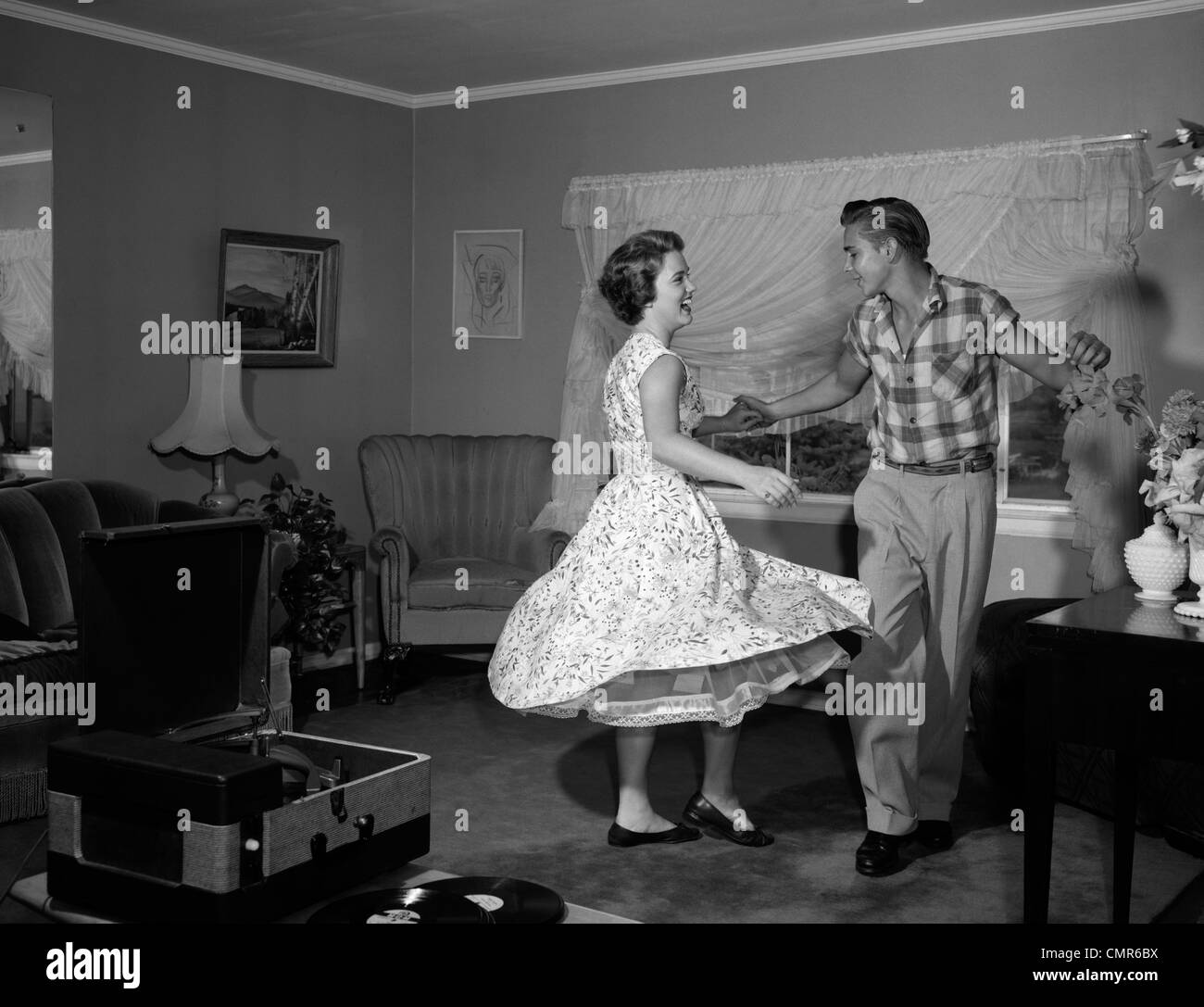 1950s 1960s TEEN COUPLE DANCING JITTERBUG IN LIVING ROOM