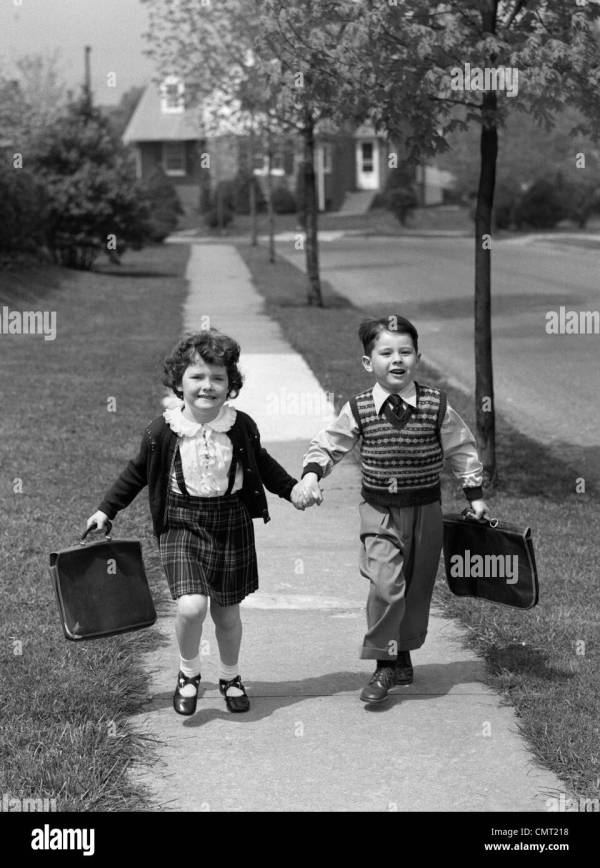 1950s BOY AND GIRL CARRYING BOOK BAGS WALKING TOGETHER