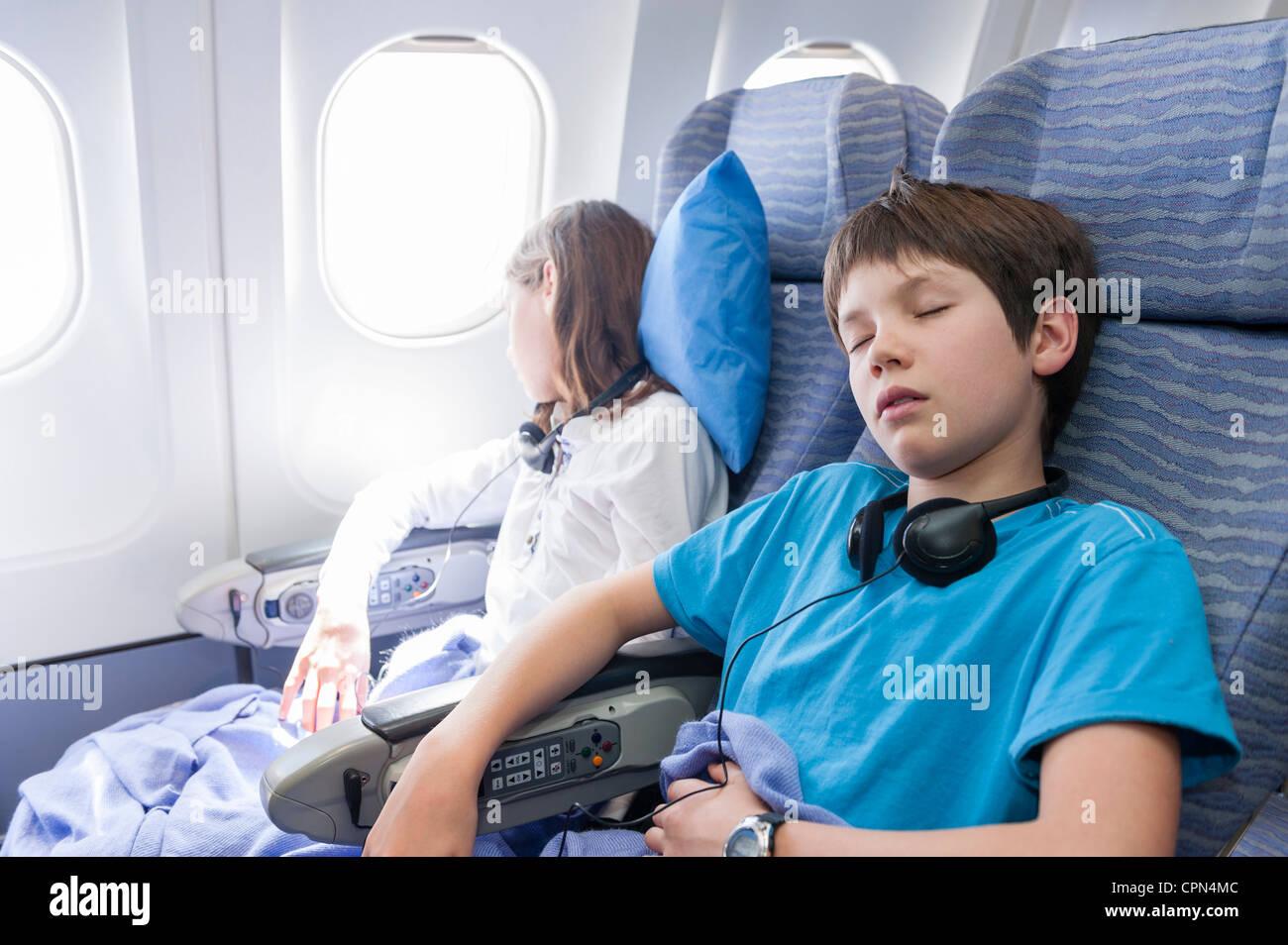 Children sleeping on airplane Stock Photo Royalty Free