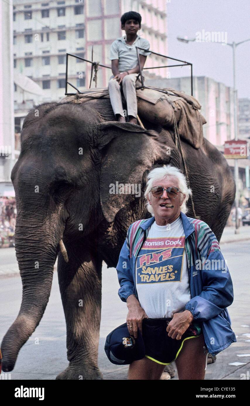 "Sir Jimmy Savile, OBE pictured in Mumbai, India in 1992. The disc jockey and radio and TV personality was ""Running Stock Photo"