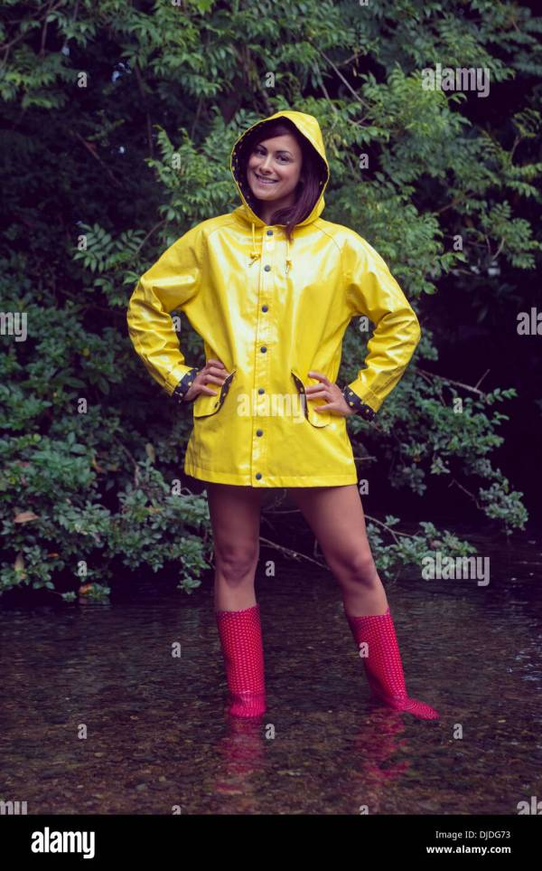 Smiling Woman In Yellow Raincoat And Red Gumboots