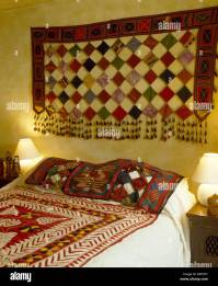 Patchwork wall hanging on wall above bed with Indian ...