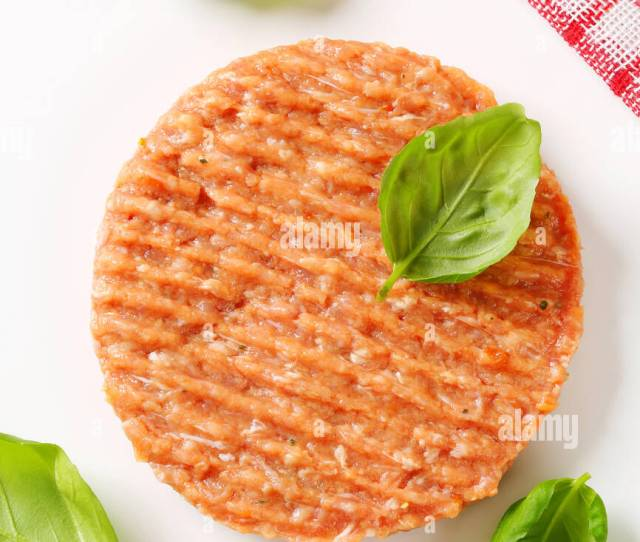Raw Burger Patty With Fresh Basil Leaves