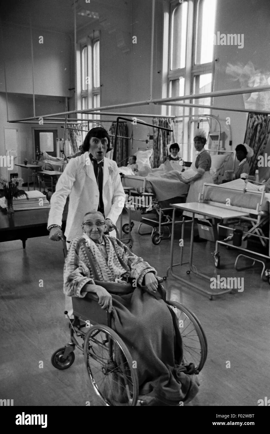 Jimmy Savile pushing someone in wheelchair in 1968. Stock Photo