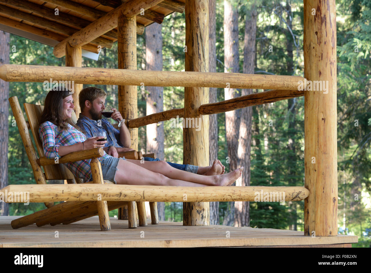 swing chair for porch reclining garden chairs the range couple enjoying a glass of wine on log cabin at stock photo, royalty free ...