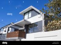 Modern gray and white house with blue sky and wooden ...