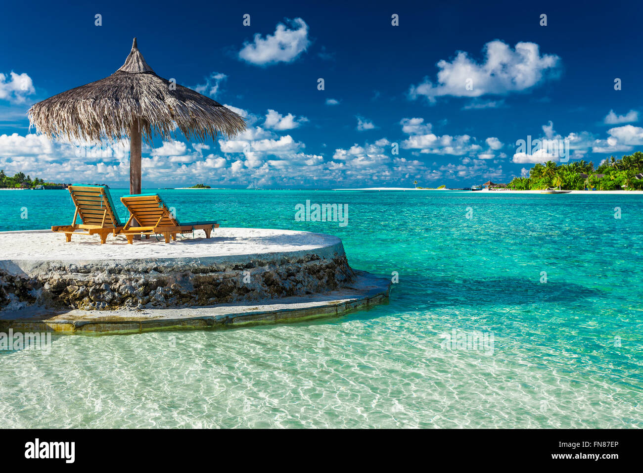 Two beach chairs under umbrella with ocean view in