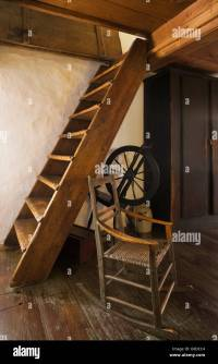 Old wooden rocking chair and spinning wheel next to attic ...