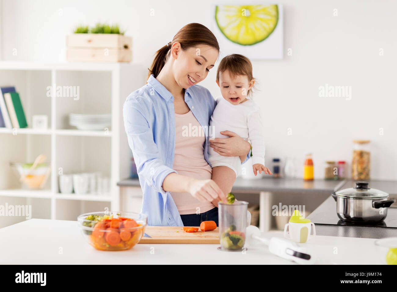happy mother and baby cooking food at home kitchen Stock