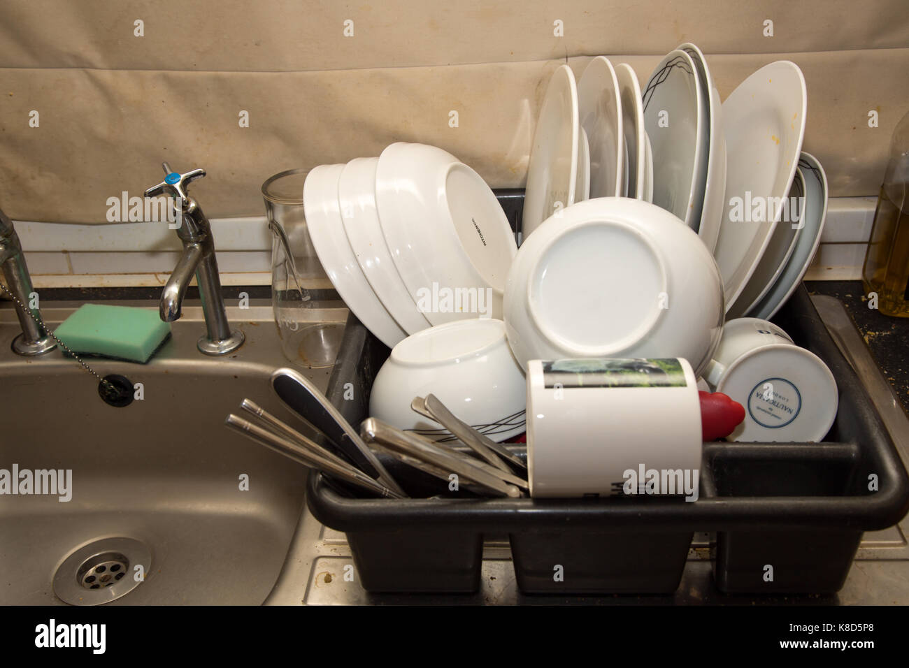 kitchen draining board storage organizers domestic full of washed crockery and cutlery