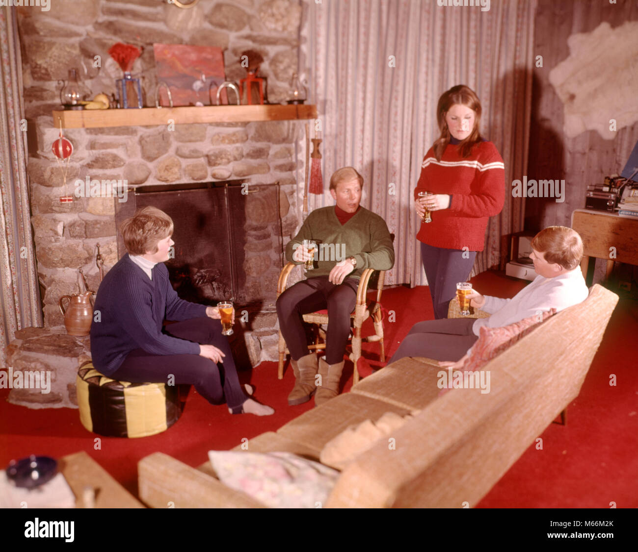 Couple Relaxing In Front Of Fireplace Man Looking At Woman Stock Married Couple 1960s Stock Photos & Married Couple 1960s