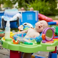 High Chairs For Small Babies Kid Adirondack Chair Plans Cute Baby Asleep Outdoors In The Garden A Colorful Surrounded By Plastic Toys And Watched Over Parents Relaxing An Above Ground