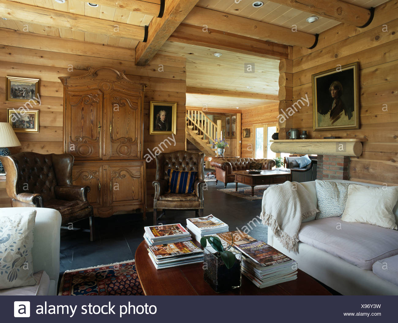 wing chairs for living room ergonomic chair dublin white sofas in with timbered walls and cupboard between brown leather