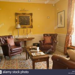 French Country Living Room Colors Ceiling Design Kerala Brown Leather Armchairs And Patterned Tiled Floor In Yellow With Gilt Framed Picture Above Dado Rail