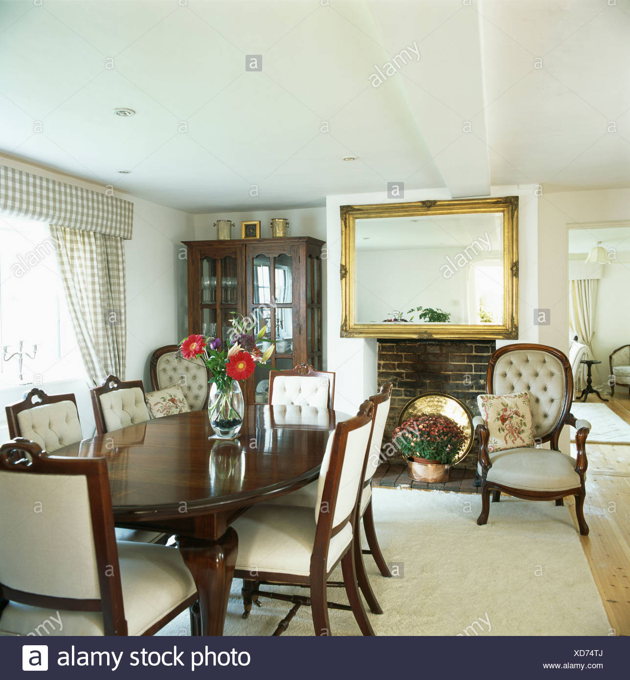 cream upholstered dining chairs recliner wooden chair and antique table in white country room with large gilt mirror above fireplace