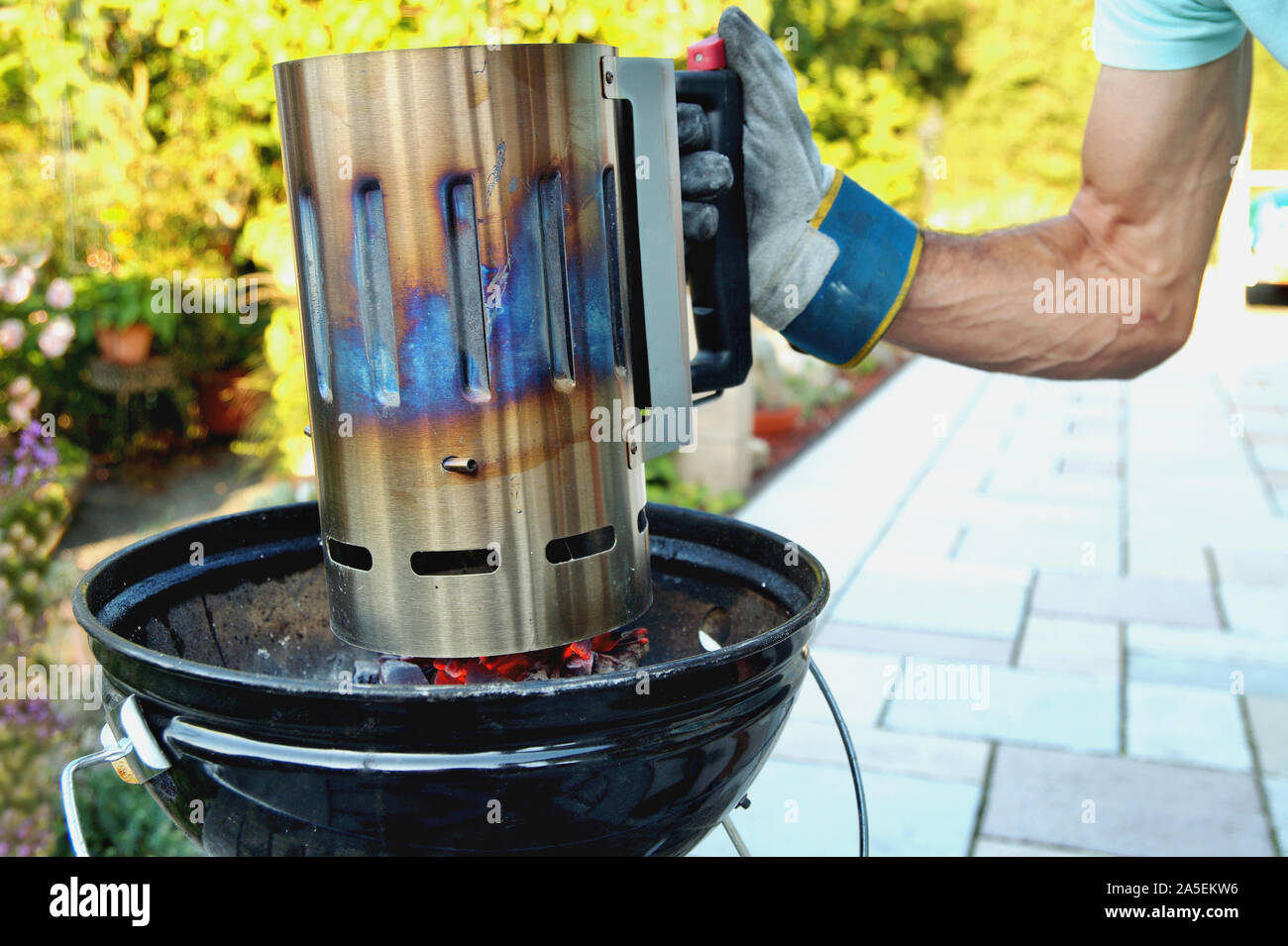 https www alamy com kindling coals male hand holding the chimney and lighting it using coal chimney starter lighting the flame on the grill grate terrace and garden image330393202 html