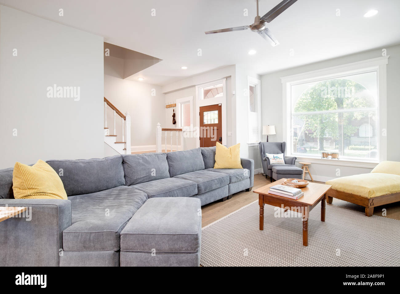 A Luxurious Living Room In A Downtown Chicago Neighborhood The Room Features A Large Grey Couch With Yellow Accent Pillows And An Area Rug Stock Photo Alamy