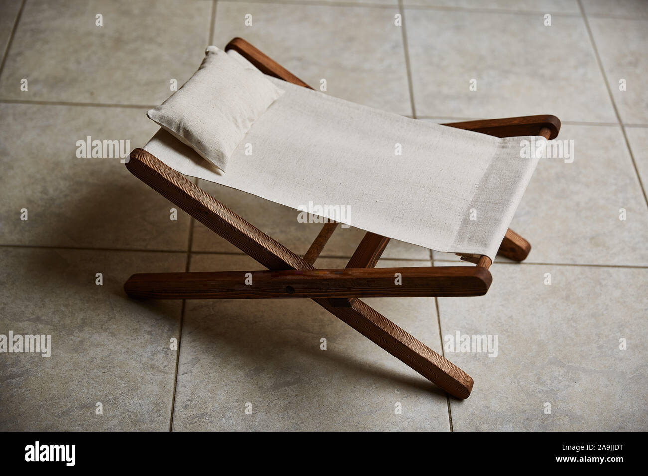 A Wooden Hammock With Beige Linen Fabric Stands On A Ceramic