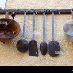 Vintage Or Antique Collection Of Old Kitchen Utensils Hanging On Wall Rack Including Pans Drainers Spatulas Stock Photo Alamy