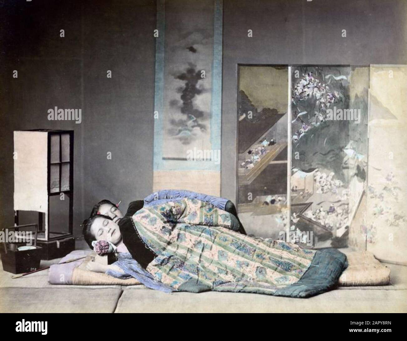 https www alamy com sleeping in japan two women sleeping under a quilted blanket in a room with painted room screen wall roll paper painting and a paper lantern as a night light their head is resting on a japanese pillow this consists of a wooden box of about ten to thirteen centimeters high on the box is a small pillow often this is provided with rolled paper as pillowcase the box can also serve as a toilet bag undated around 1880 1890 place unknown hand coloured albumin photo belonging to a series of 42 prints in the collection of spaarnestad photo by felice beato kusakabe kimbei or raimund image341119065 html