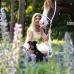 A Pretty Young Woman And Her Chestnut Horse Stand In A Beautiful Forest Setting Stock Photo Alamy