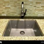 Stainless Steel Kitchen Sink And Faucet With Light Marble Countertop And Green Glass Wall Tiles Stock Photo Alamy