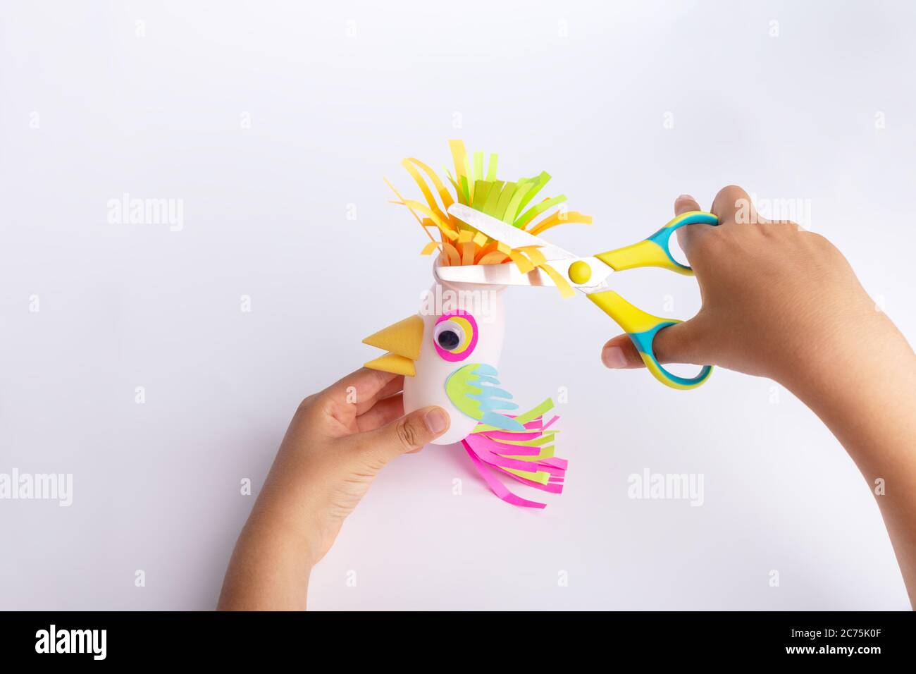 Child Makes A Parrot Craft From Paper And Recycled Yogurt Bottle Diy Kindergarten Or School Children Activity Funny Bird Craft For Kids Stock Photo Alamy