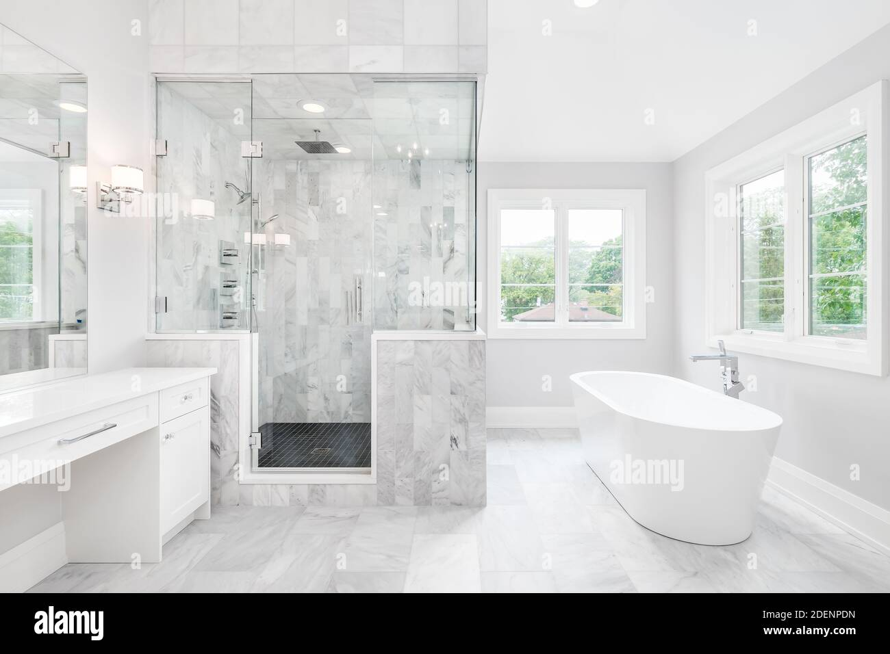 https www alamy com a large luxurious bathroom with a stand alone tub white vanity and a glass stand up shower with marble tiles and bench seat image387711905 html