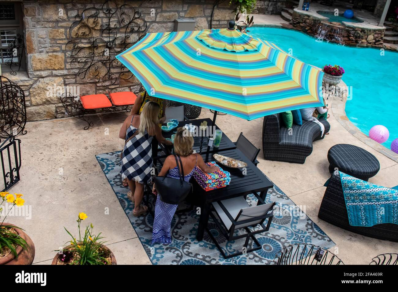 https www alamy com tulsa ok usa 5 20 2018 women standing around patio table beside swimming pool with nice outdoor furniture top view image419288179 html