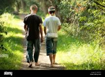Two Young Boys Walking Forest Track In Bare