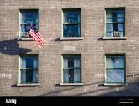 Apartment windows in building with American flag flying ...