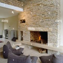 Grey Modern Armchairs Wingback Nailhead Chair Lit Fire In Fireplace Stone Wall Of Barn Conversion, With Stock Photo: 10205639 - Alamy