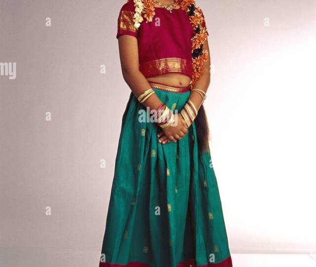 Young South Indian Girl Standing White Background Wearing Traditional Costume Dress Ghagra Choli Skirt Top Flowers Gajra In Hair