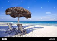 Caribbean beach scene with two chairs under shade palapa ...