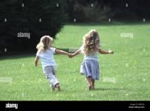 Two Little Girls Running Barefoot Grass Stock