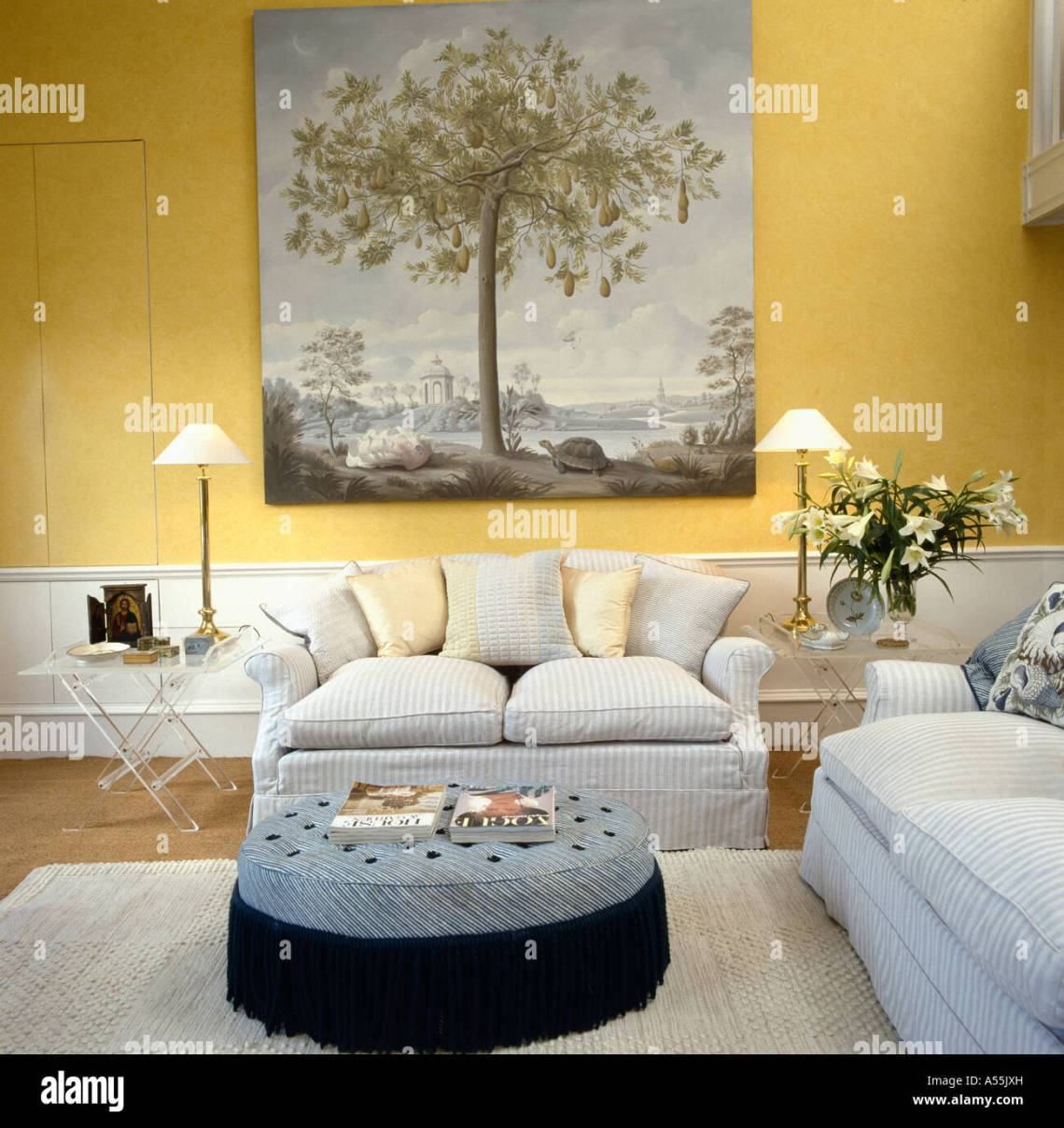 Large 18th Century Style Picture Above Pale Gray Sofa In Pale Yellow Living Room With Large Circular Upholstered Stool Stock Photo Alamy