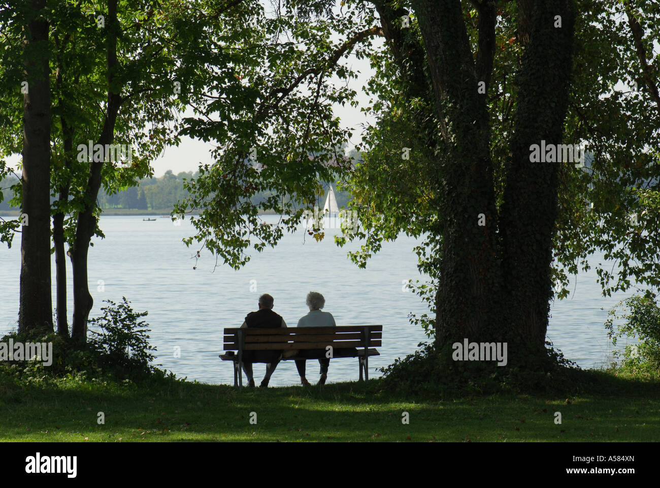 Old Married Couple Sitting On A Park Bench At Lake