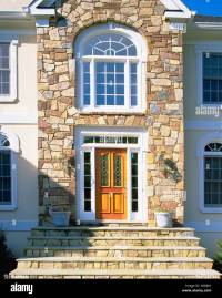 Front entrance of elegant house with stone facade and ...