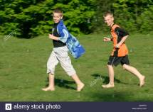 Two Boys Running Barefoot Meadow Stock