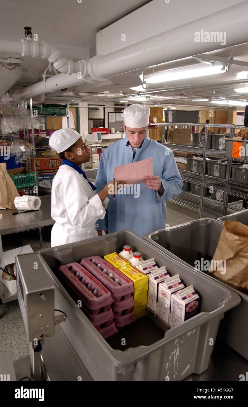 Chef and cook look over inventory in massive kitchen at restaurant Stock Photo Royalty Free