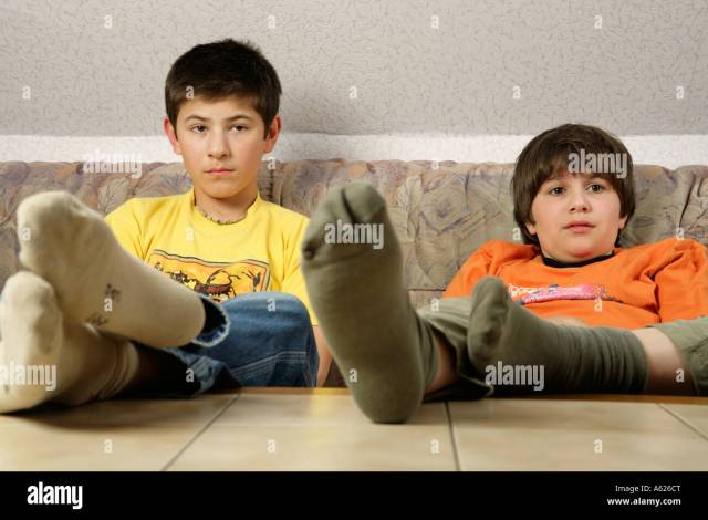 Portrait Of Two Young Boys Glued To The Television With Their Feet On The Table