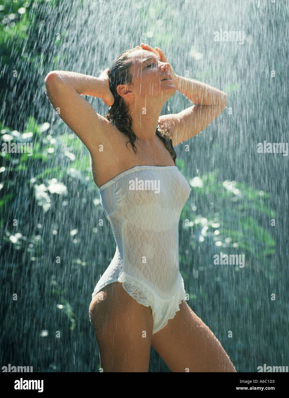 girl in white swimsuit standing in outdoor shower Stock