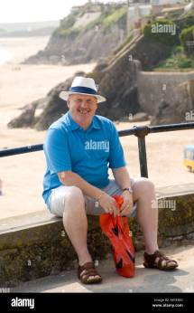 Middle Aged Man In Sitting Wearing Straw Sun Hat Shorts