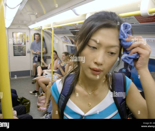 Asian Woman Tourist Standing In Heat Of London London Underground Tube Train Female Wiping Sweat From Brow
