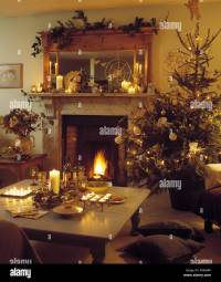 Christmas tree beside fireplace with lighted fire in warm ...