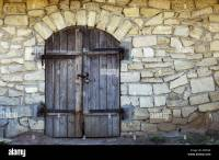 Old stone wall with an arched wooden door texture Stock ...
