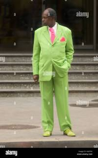 A man in a bright green suit and pink tie standing on the ...
